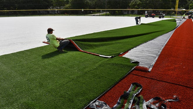 """Artificial turf installers Alejandro Colis (left) and Mike Colis, with Fields Inc., of Canton, Georgia, position a roll of Shaw Sports Turf on June 19, 2017, inside the new Jake Owen Field under construction at 2665 12th Ave. in Vero Beach. """"This is a Cal Ripken Sr. Foundation and Jake Owen Field, and its donations from Kevin Harvick and Jake Owen, and Cal Ripken Sr. They donated the money to get this field going,"""" said Carlos Abad (not pictured), superintendent of Fields Inc. """"It's a baseball field for youth leagues."""""""