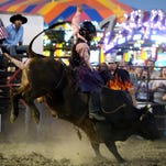 Dustin Boquet hangs onto his bull for more than eight seconds Wednesday during bull riding at the Pensacola Interstate Fair put on by J.C. Kitaif Pro Rodeos..