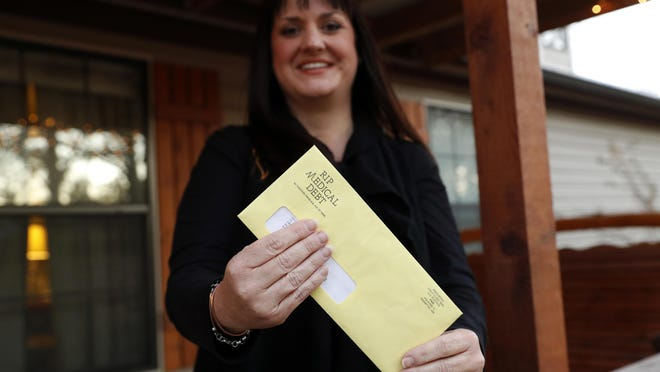 In this Dec. 20, 2018 photo, Reagen Adair holds on to an RIP Medical Debt yellow envelope as she poses for a photo at her home in Murchison, Texas. The co-founders of RIP Medical Debt buy millions of dollars in past-due medical debt for pennies on the dollar. But instead of hounding people to pay, they send letters saying the debt is erased, no strings attached.