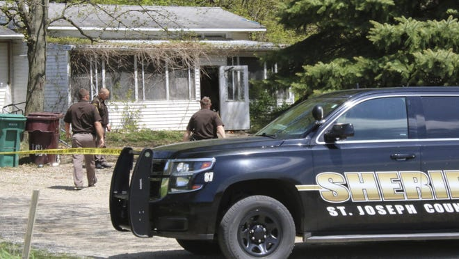 In this Monday, May 6, 2019 photo, St. Joseph County Sheriff deputies stand outside the site where a woman was fatally shot in Fawn River Township, Mich. Authorities say a 9-year-old is suspected in the shooting of a woman in her southern Michigan home.