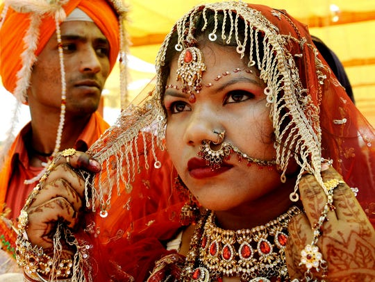 An Indian bride sits with her groom during a mass marriage