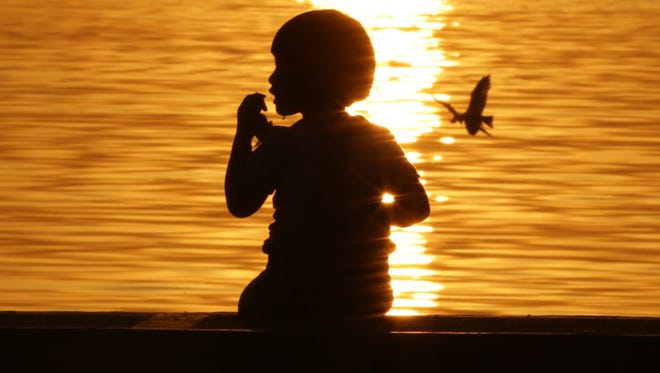 A child enjoys a snack at sunset at a breakwater on Jan. 16 in Manila, Philippines. Investigators smashed an international pedophile ring that streamed live images of child abuse from the Philippines.
