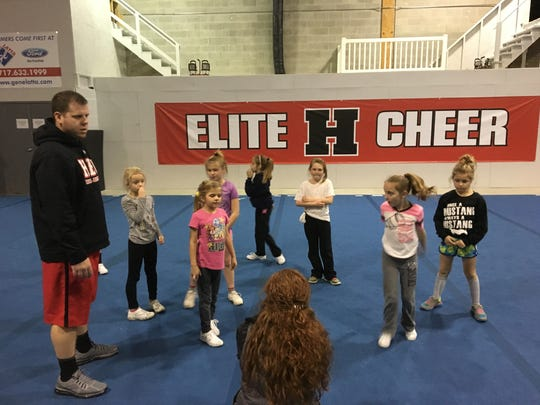 Hanover Elite Cheer coaches Chris Topper, left, and Sara Loy address their 8-and-under team.