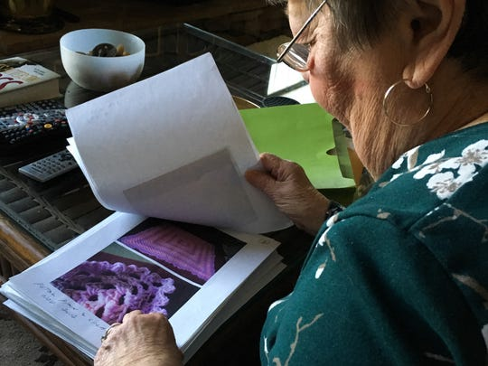 Maryrose Schwartz goes through photos of blankets she has made for Project Linus on Jan. 6 in her Greencastle home.