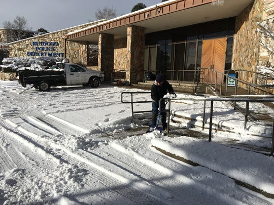Village of Ruidoso worker Sergio Boyle clears the way to the visitors entrance at the Ruidoso Police Department.