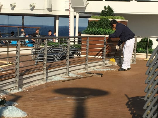 A crew member sweeps up broken glass on a deck area