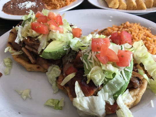 Two sopes (thick discs of hand-pinched masa dough) are topped in refried beans and carnitas at Two Amigos in Cape Coral.