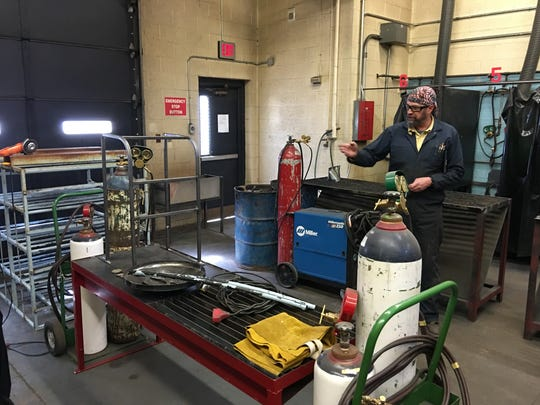 RHS teacher Dave Mader shows school board members a special frame welded by his students that a disabled skier can use like a walker on the slopes.