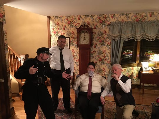Officer O'Hara (Jeff Leinbach) regales Mortimer Brewster (Rich Knight, seated) with the plot of his play, as Jonathan Brewster (Matthew Henning) and Dr. Einstein (Patrick McNamee) look on.