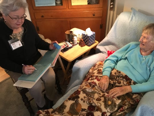 Mary Jane Sasser, a CAREGiver for Home Instead Senior Care, documents the correct time and medication for Betty Carter, a client, during a home visit.