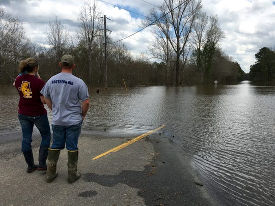 William and Joy Cook, holding son Matthew, look at a flooded Highway 500 east of Georgetown in Grant Parish, waiting to take a boat Sunday to check on their home off the highway.