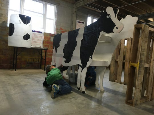 """A child milks a """"cow"""" last fall at The Pickwick Place,"""
