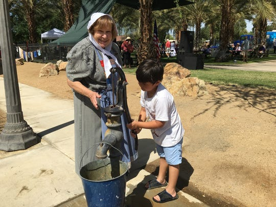 A Coachella Valley History Museum volunteer demonstrates an antique water pump for children attending the Coachella Valley Heritage Festival on March 19, 2016.