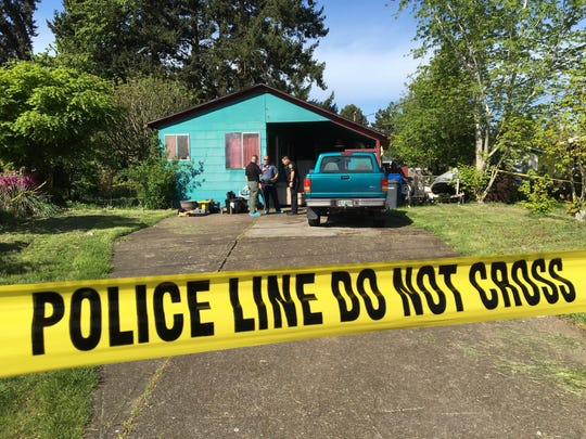 Police officials work the scene of a reported stabbing on Friday, April 15, outside a home in Keizer.