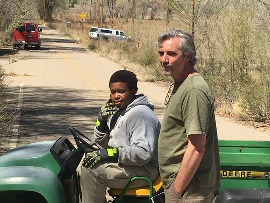 Juvenile Justice Board director Ted Allen, right, chats with AmeriCorps team member Kirby Aristide of North Beach Miami, FL, as they survey team progress clearing brush at Fort Stanton.