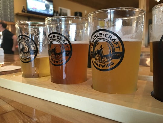 A flight of beer from Stable Craft Brewing outside