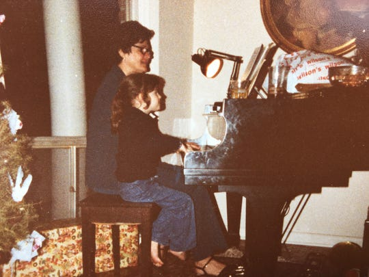 Ruth Bowen plays piano with one of her children.