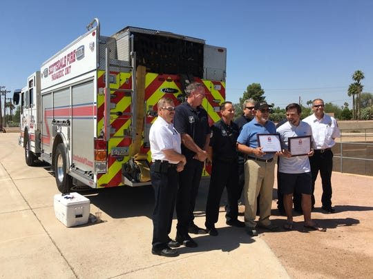 Danny Ortega (center left) and Tyler Moore hold certificates from the Scottsdale Fire Department recognizing their efforts in helping to rescue Jim Palecek and his dog, Duke, from a canal.