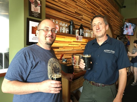 River's Edge Brewing Co. co-owners Ryan Wiltse, left, and Tom Ouvry both hoist a Dirty Frank Stout, the beer that received a bronze medal at the 2016 World Beer Cup. Photo taken May 25, 2016 at the brewery in Milford.