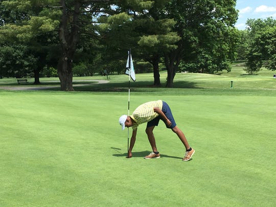 Spackenkill's Stanley Garrant retrieves his ball after a hole-in-one during the Coaches Invitational golf tournament.