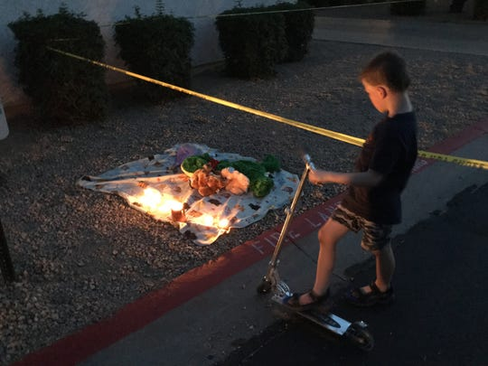 A 7-year-old boy stands near a memorial for his friends,