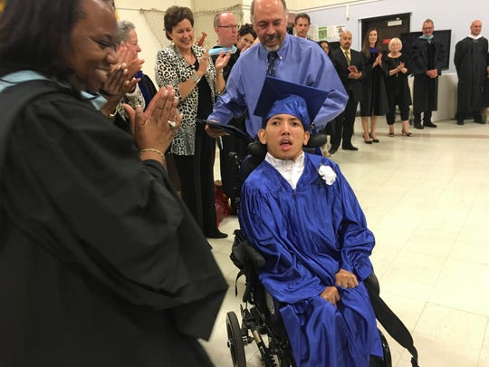 Superintendent Traci Davis cheers on Picollo student Royce Oshira-Miguel at the school's graduation ceremony on June 7, 2016.