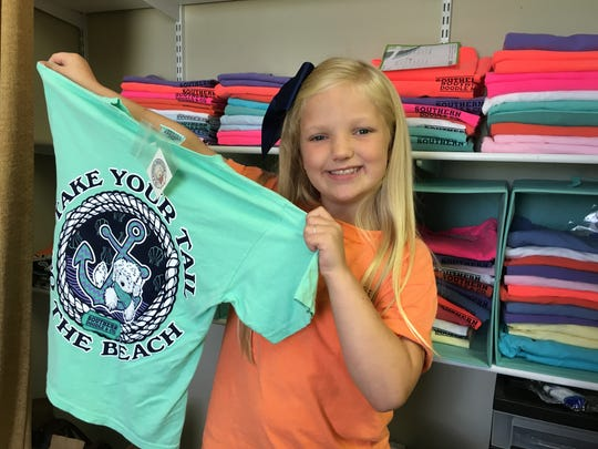 Anna Gleason, 8, holds one of the designs she created