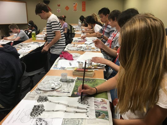 Students create Chinese art during a cultural exploration