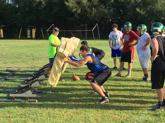 Island Coast offensive linemen hit the sled Monday as fall camp opened.