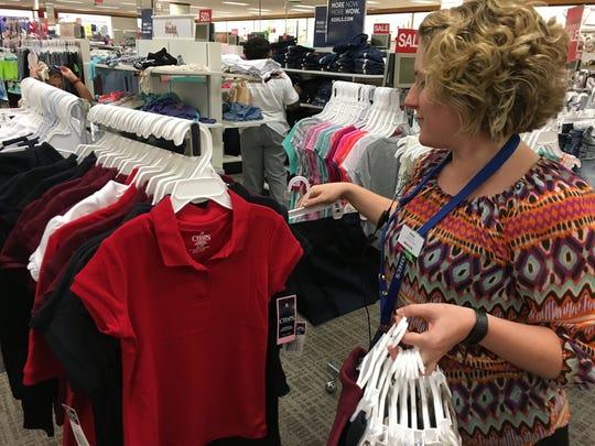 Employee Amy Moman arranges a school uniform display