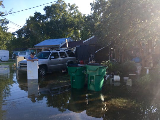Tracie Matlock stands with a table in rising water surrounding her home and vehicle on North Avenue H in Crowley. She said water entered her home Sunday night and was up to the baseboards by 8 a.m. Monday.