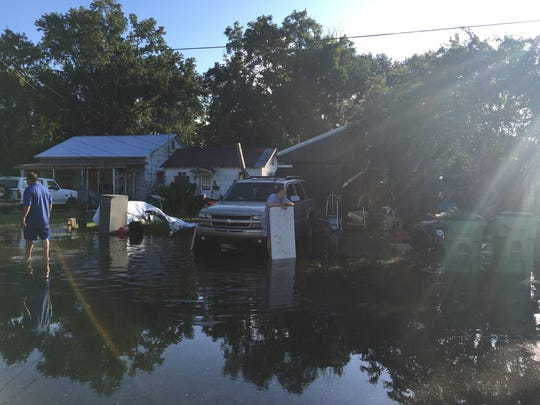 Wayne and Tracie Matlock walk through water surrounding their home on North Avenue H in Crowley Monday.