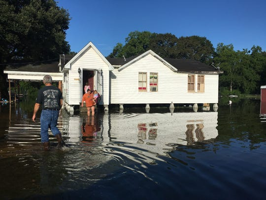 Barry and Mindy Adams and their children look at water surrounding their house on North Avenue H in Crowley Monday morning.
