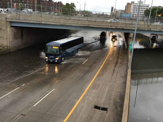 Motorists drive through a flooded I-75 at Grand River on Tuesday, Aug. 16, 2016 in downtown Detroit.