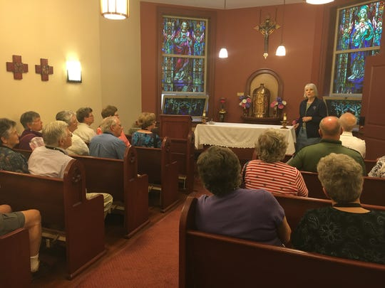 Local travelers listen to Sister Marilyn Ellickson in the Leo House chapel during a recent tour.