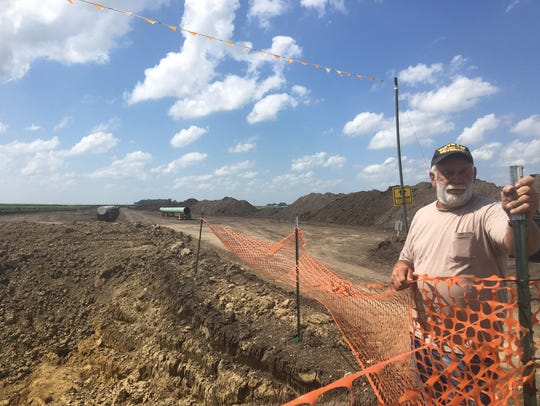 Francis Goebel stands near the construction site for