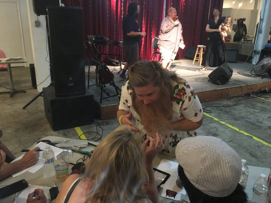 Kateri Fikar presents her fake beard to judges at Saturday's Bearding Man contest in Shippensburg. She won second place in the Fake Beard category.