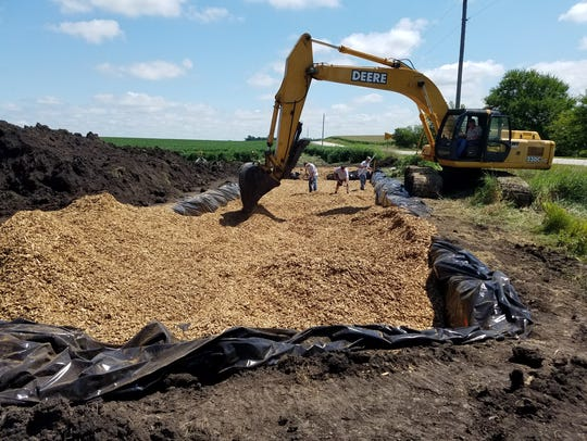 Contractors spread wood chips throughout the trench