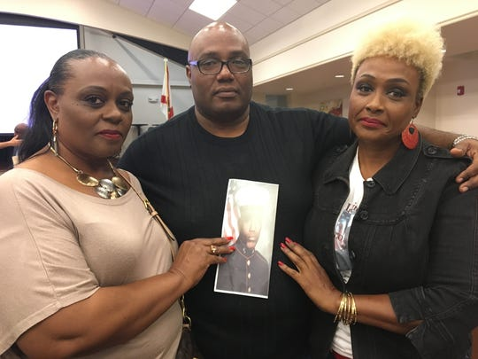 Veronica Jones-Greene, Kevin Jones and Melissa Jones pose with a picture of their brother Keith Jones. Keith was killed in Fort Myers almost 20 years ago. A Cape Coral woman was arrested in October as a suspect in Jones' homicide.