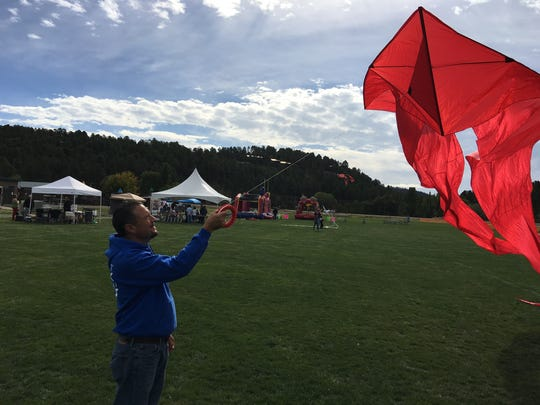 Parks and Rec Director Rodney Griego launches one of the first kites in the air Sunday to welcome festival participants and show them that the wind is waiting.
