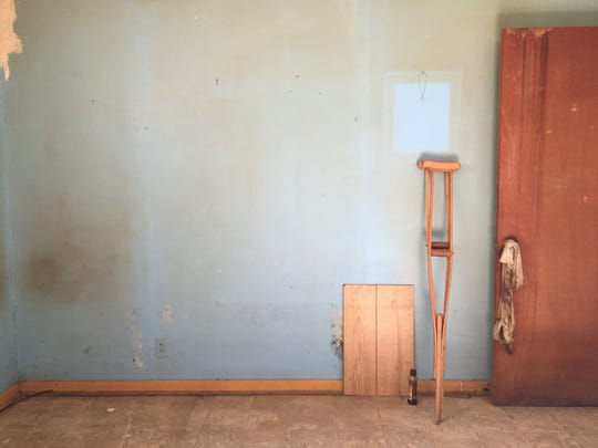 Mold is visible behind a panel in an empty room in Elizabeth Splond's home. Large patches are present in closets adjacent to the bedroom.