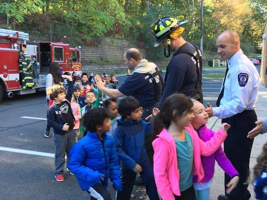 "Kind High Five - ""Kindergarten students high five Watchung firefighters after a tour of a firetruck."""
