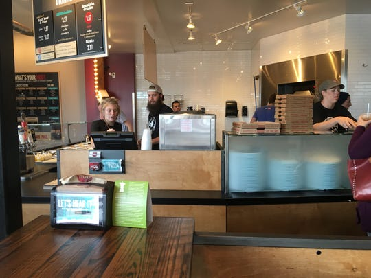 Employees whip out orders at MOD Pizza in Fort Collins.