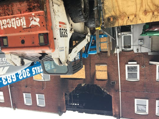 The top floor of the rear wall of a rowhome in Canby Park was demolished Thursday. A fire in the home killed two firefighters in September.