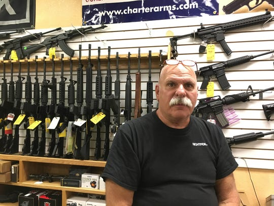 Sam Scarmardo sits behind the counter at his gun shop,