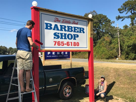 Danny Carpenter's daughter and her boyfriend paint new sign for barbershop.