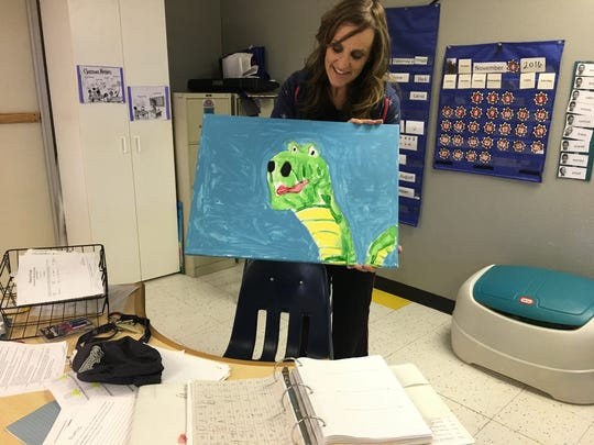 Jeri Dieter of the Newton Learning Center shows off the artwork of an elementary school student.