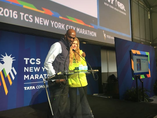 "Lori Riggles, a Montgomery Catholic teacher, stands with  Michael Rodgers, vice president of development and philanthropy of the New York Road Runners,  as she receives the NYRR ""Team for Kids"" Spirit Award in New York City, NY, on Saturday, Nov. 5, 2016. Riggles overcame serious injuries after she was hit by a truck while running on April 17. She will run the New York City Marathon on Sunday, Nov. 6, 2016."