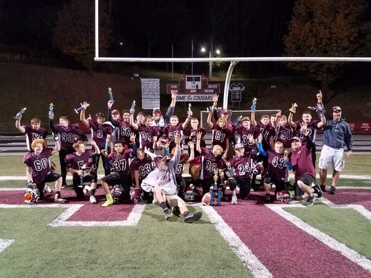 The midget division Warhorses celebrate a Super Bowl victory and an 11-0 season on the field at Asheville High School on Nov. 6.