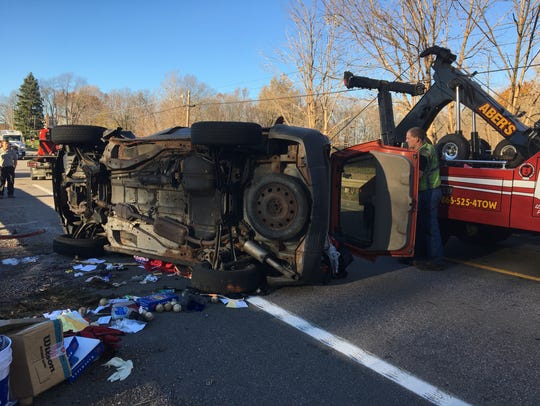 A tow truck begins to flip over a Ford Escape involved